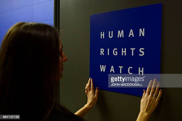 A woman puts a logo of USbased rights group Human Rights Watch on the door as she prepares the room before their press conference to release their...