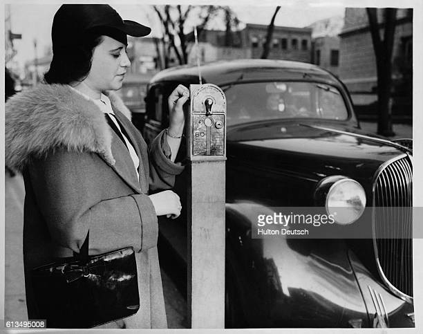 A woman puts a nickel into the parking meter at White Plains in order to have another hour's car parking