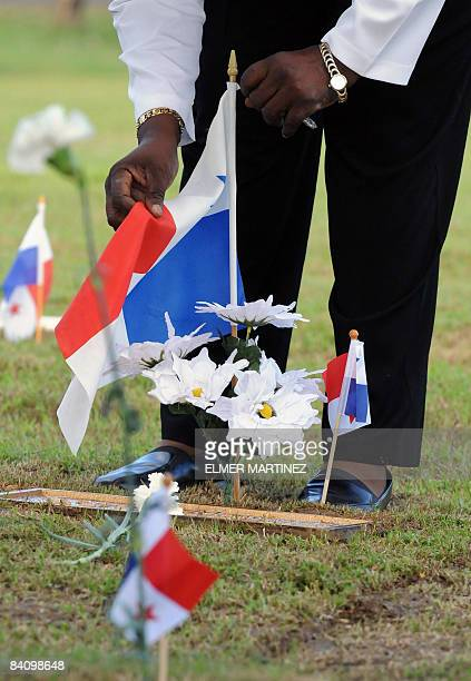 A woman puts a Panamanian flag over the grave of a soldier killed in the 1989 US invasion to Panama at the Jardin de la Paz cemetery in Panama City...