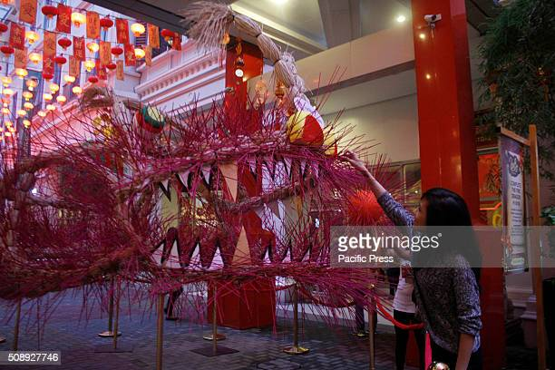 A woman puts a stick of incense on the Fire Dragon frame at a mall in Binondo Filipinos enjoy Chinese display at Lucky Chinatown in Manila ahead of...