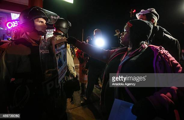 A woman puts a wanted poster on riot shield of a police officer as people gather in front of the Ferguson Police Department on November 29 2014 to...
