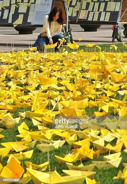 A woman puts a yellow paper ship forming the shape of a heart at a memorial for victims of the 'Sewol' ferry in Seoul on May 7 2014 Recovery teams...