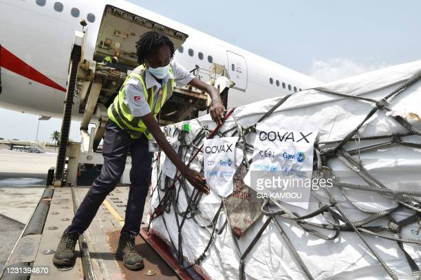 Woman puts Covax stickers as workers unload a shipment of AstraZeneca Covid-19 vaccine from a plane at Felix Houphouet Boigny airport of Abidjan on...