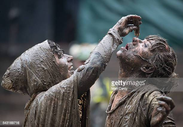 A woman puts eye drops in her friends eye after they rolled in the mud following a tomato fight at the Glastonbury Festival 2016 at Worthy Farm...
