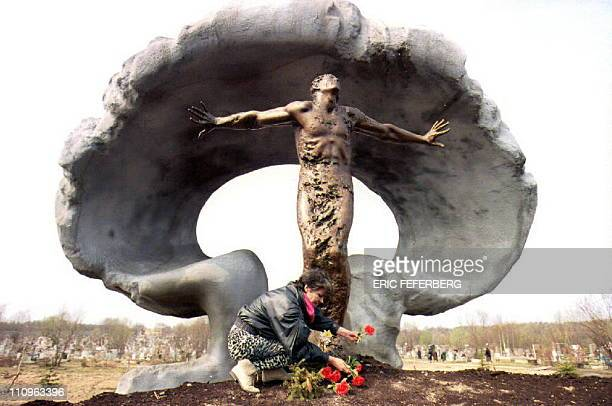 A woman puts flowers at the new memorial to victims of the 1986 Chernobyl nuclear power plant explosion at Mitino cemetery 27 April 1993 The memorial...