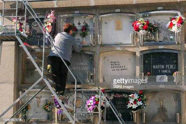 HOSPITALET BARCELONA SPAIN A woman puts flowers in the tomb of a relative on the day of all the saints a celebration in honor of the deceased Spain...