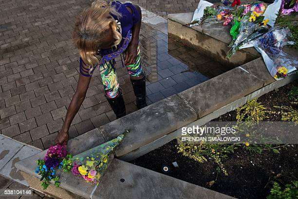 A woman puts flowers outside the Muhammad Ali center where mourners created a makeshift memorial for the boxer on June 4 2016 in Louisville Kentucky...