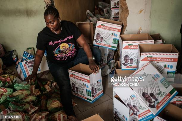 A woman puts food donation into boxes bearing the faces of Nigeria's incumbent President Mohammadu Buhari and Vice President Yemi Osinbajo in Lagos...