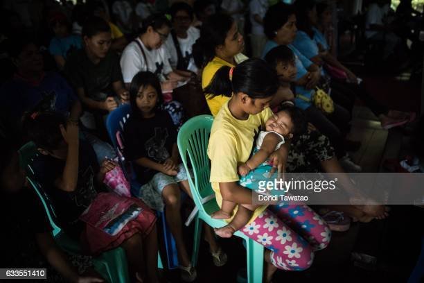 A woman puts her baby to sleep during a mass held for victims of the drug war on February 2 2017 in Manila Philippines Philippine president Rodrigo...