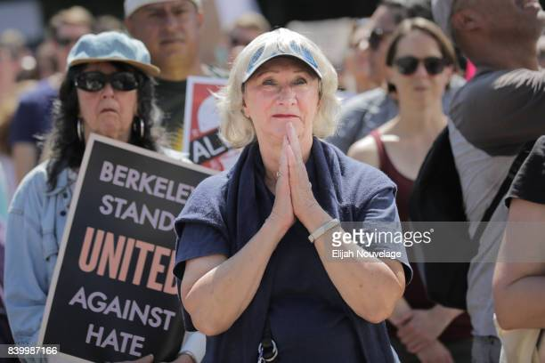 A woman puts her hands together while listening to a speaker at a peaceful gathering near UC Berkeley on August 27 2017 in Berkeley California A...