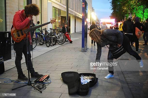 A woman puts money in a busker's guitar case at the Edinburgh Festival Fringe on August 17 2013 in Edinburgh Scotland