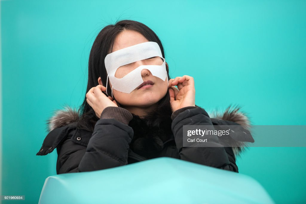 A woman puts on a hygienic face-mask before wearing a virtual reality headset as she tries a virtual bobsleigh in the PyeongChang 2018 Winter Olympics Live Site on February 21, 2018 in Seoul, South Korea. With tourists visiting from around the world, leaders from South Korea's capital as well as GyeongGi and Gangwon Provinces have agreed to work together to support the PyeongChang Olympic Games and to invigorate regional tourism.