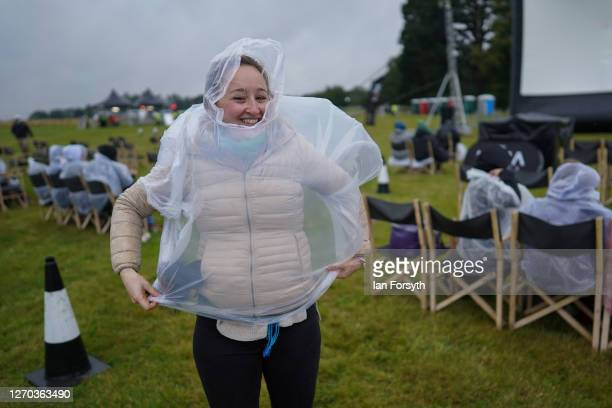 Woman puts on a plastic poncho as members of the public attend a screening of The Greatest Showman during the Luna Cinema movie experience at Castle...