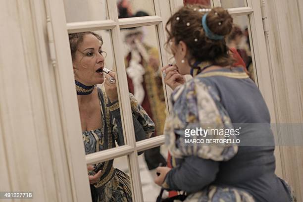 A woman puts on lipstick during the Nuit Royale event a bal in costume of the eighteenth century at the palace of Venaria Reale a former royal...
