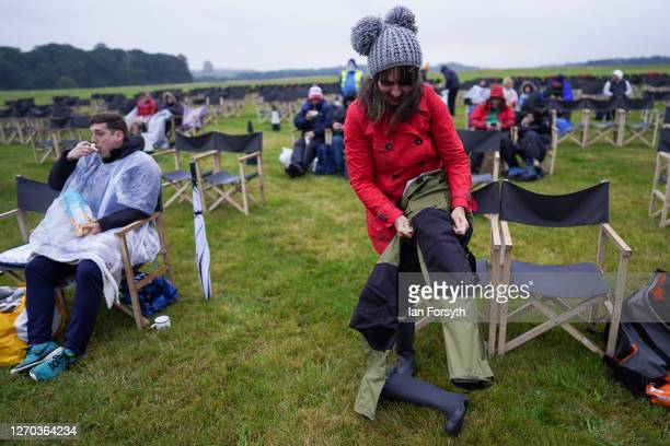 Woman puts on waterproof trousers as members of the public attend a screening of The Greatest Showman during the Luna Cinema movie experience at...