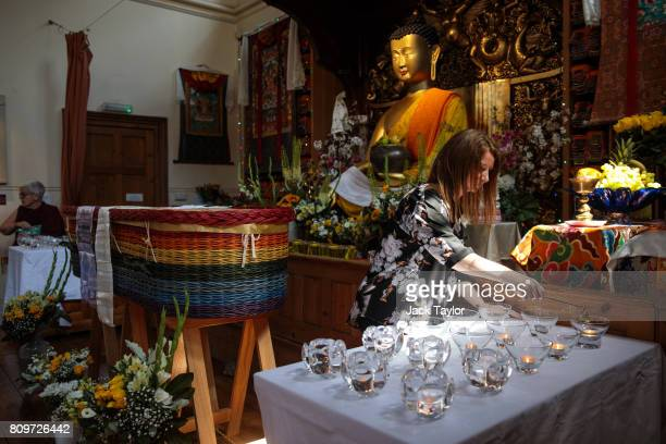 A woman puts out candles next to the willow eco coffin of Jon Underwood as it rests at the Jamyang Buddhist Centre on July 6 2017 in London England...