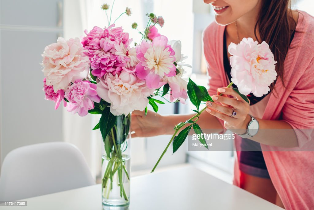 Woman puts peonies flowers in vase. Housewife taking care of coziness and decor on kitchen. Composing bouquet. : Stock Photo