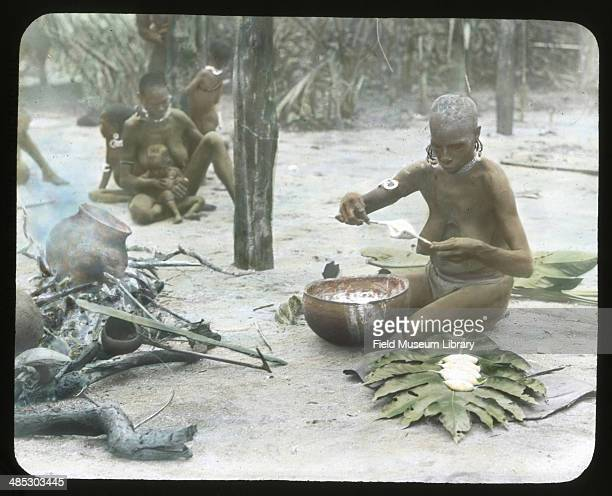 A woman puts sago mush on a banana leaf plate Sissano Papua New Guinea November 1 1909 The stirring paddle coconut dipper and hot water pot are seen...
