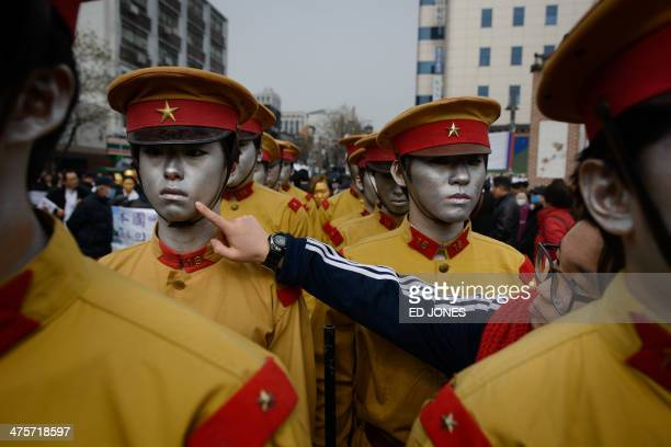 Woman puts the finishing touches of makeup on an activist dressed as colonial-era Japanese soldiers prior to a re-enactment of a 1919 crackdown in...