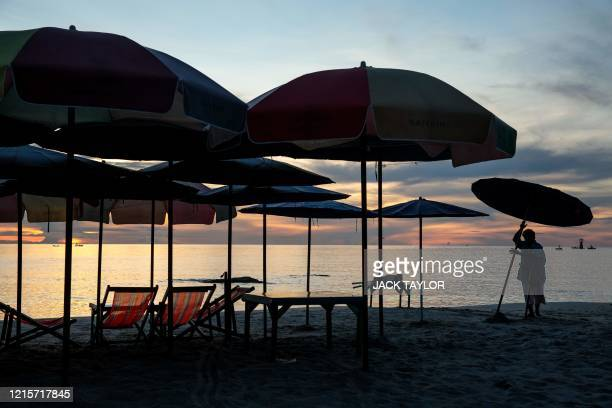 Woman puts up a beach umbrella as the sun rises on the beach in Hua Hin on May 28 as Thailand continued to ease restrictions imposed to stop the...