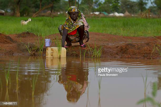 A woman puts water into plastic jug from a muddy pond July 17 2012 in Jamam refugee camp South Sudan Many refugees choose to gather rain water that...