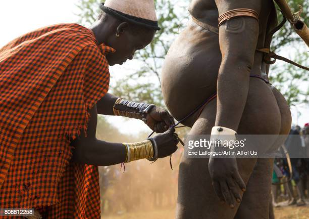 Woman putting a belt to a Bodi tribe fat man during Kael ceremony Omo valley Hana Mursi Ethiopia on June 2 2017 in Hana Mursi Ethiopia