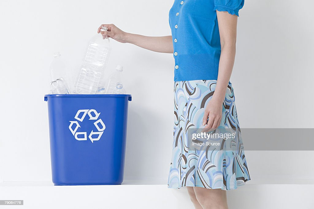 A woman putting a bottle in a recycling bin : Stock Photo