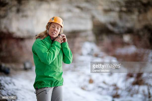 woman putting a helmet on, getting ready to ice climb. - green coat stock pictures, royalty-free photos & images