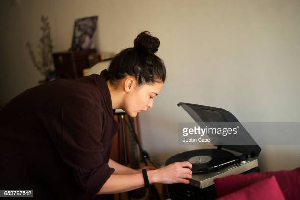 woman putting a record on the turntable - topknot stock pictures, royalty-free photos & images