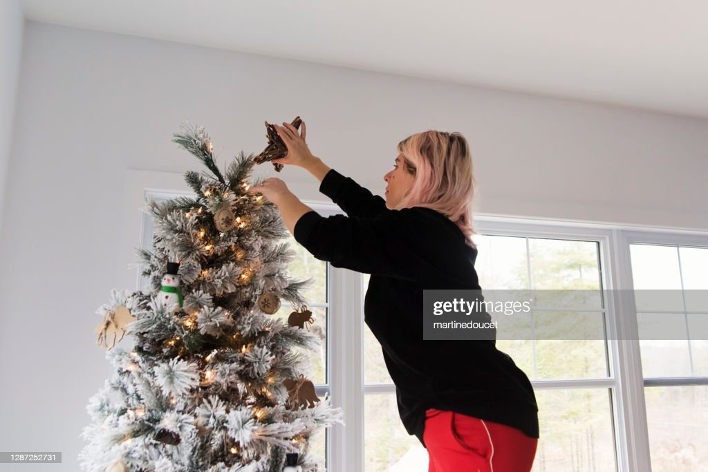 Woman putting a star on top of the Christmas tree. : Stock Photo