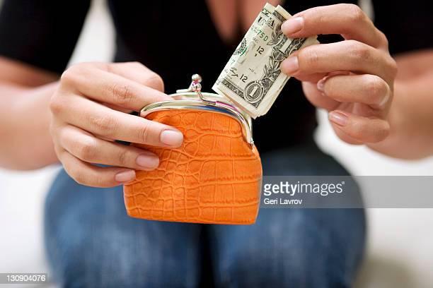 Woman putting a US $1 bill into a purse