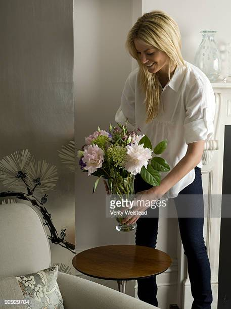 Woman putting a vase of flowers on a table