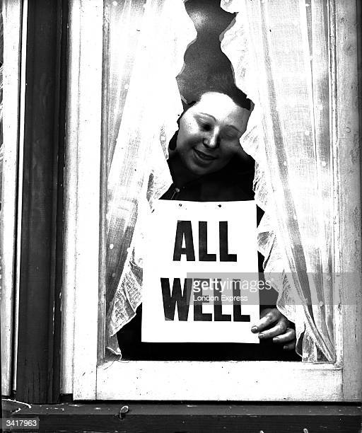 Woman putting an 'All Well' sign in her window during the Blitz.