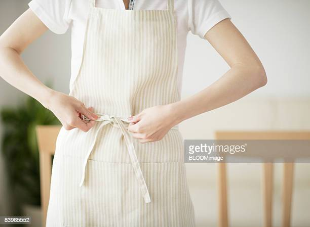 Woman putting apron on