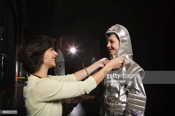 woman putting astronaut costume on child - school play stock photos and pictures