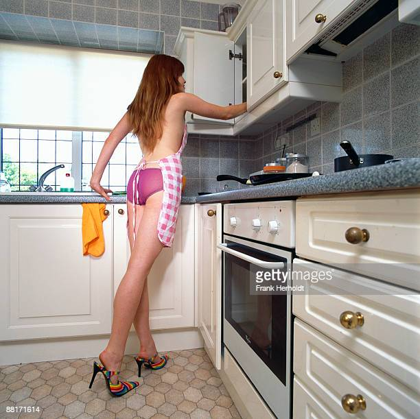 Woman putting away dishes in underwear