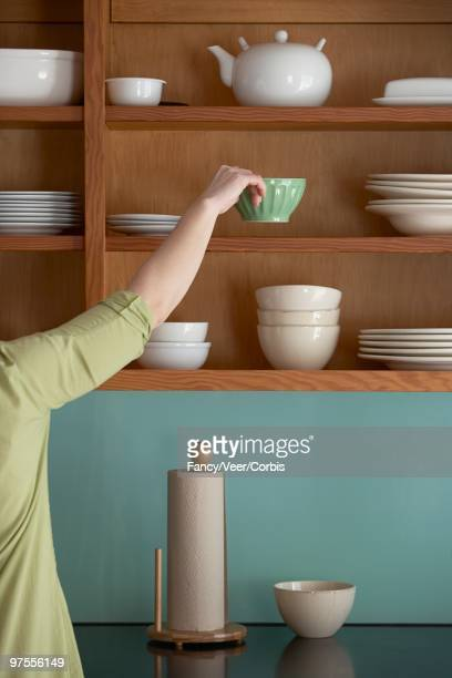 Woman Putting Away Dishes