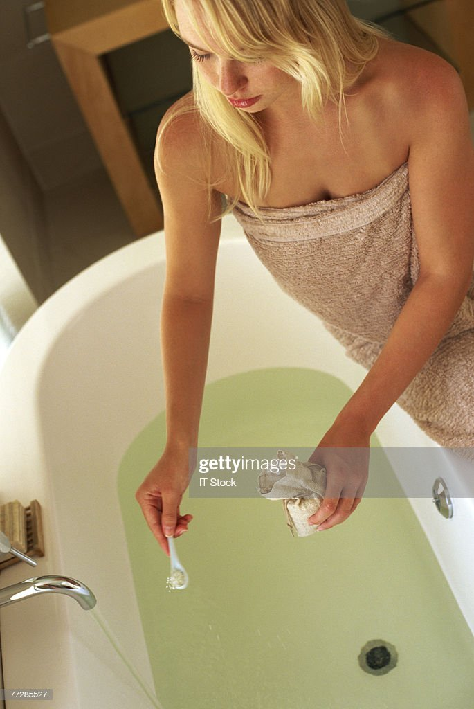 Woman putting bath salts into bath : Stock Photo