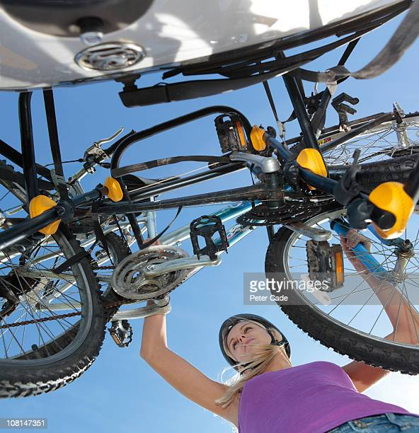 woman putting bikes onto bike rack on car