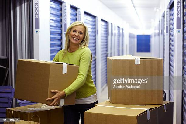 woman putting boxes in storage - self storage stock pictures, royalty-free photos & images