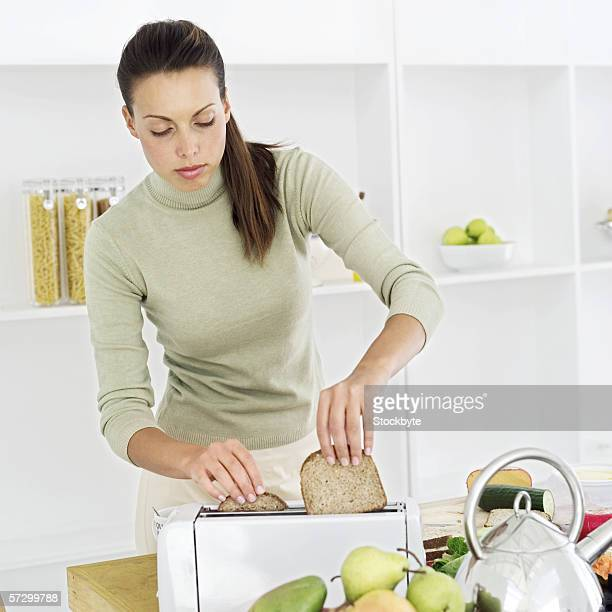 Woman putting bread in an electric toaster