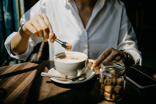 Woman putting brown sugar cube into coffee and ready to enjoy it on a fresh morning - gettyimageskorea