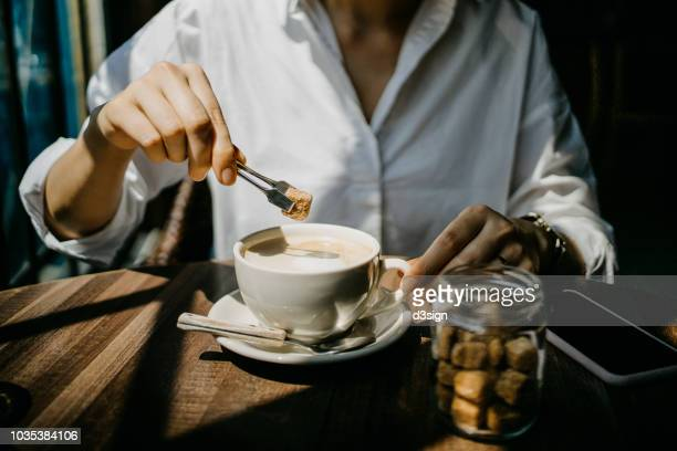 woman putting brown sugar cube into coffee and ready to enjoy it on a fresh morning - caffeine stock pictures, royalty-free photos & images