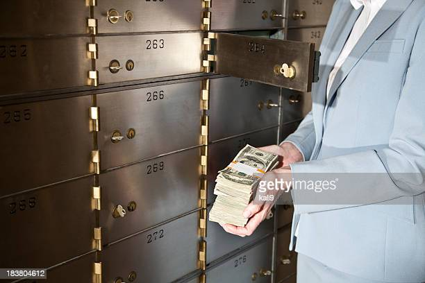 Woman putting cash in safety deposit box