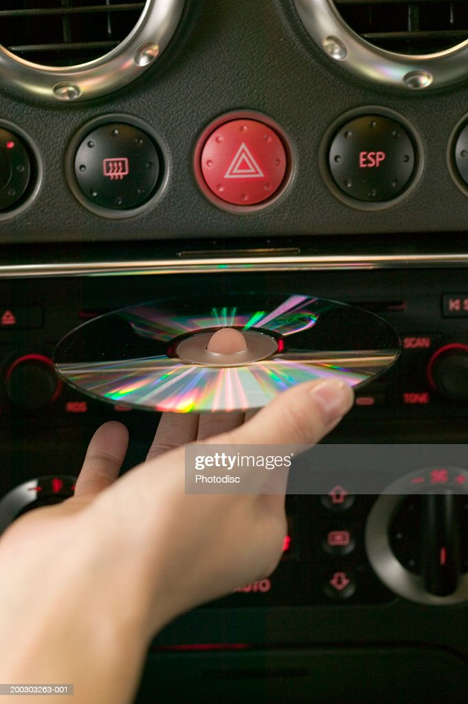 woman putting cd in car stereo rear view mid section closeup stock