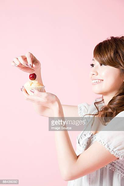 Woman putting cherry on cake