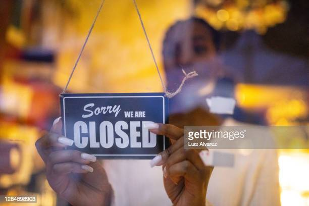 woman putting closed sign on door of coffee shop - government shutdown stock pictures, royalty-free photos & images