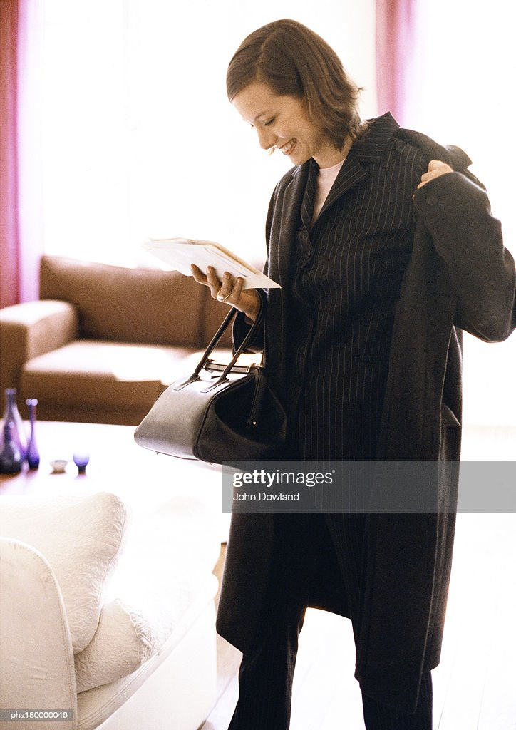 Woman putting coat on while reading : Stockfoto