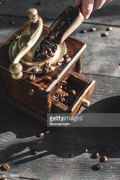 Woman putting coffee beans in vintage coffee grinder