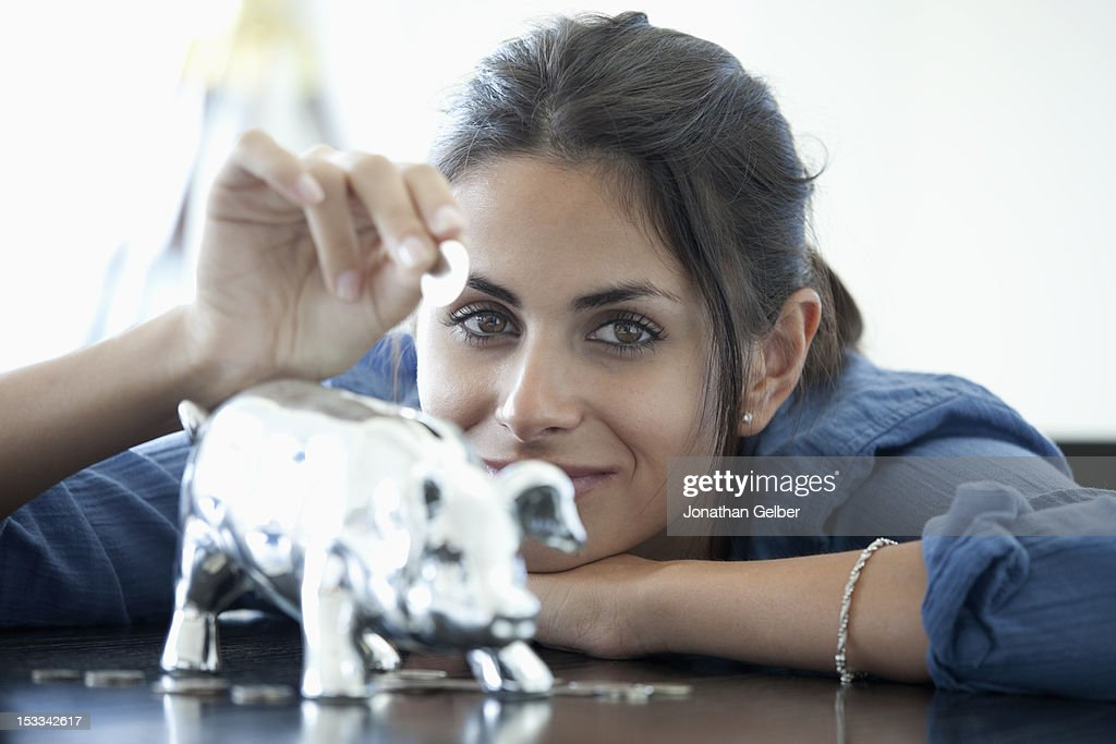 Woman putting coin into piggy bank : Stock Photo